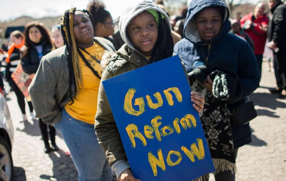 Um garoto leva na manifestação de Washington um cartaz que pede a reforma na política de armamentos.