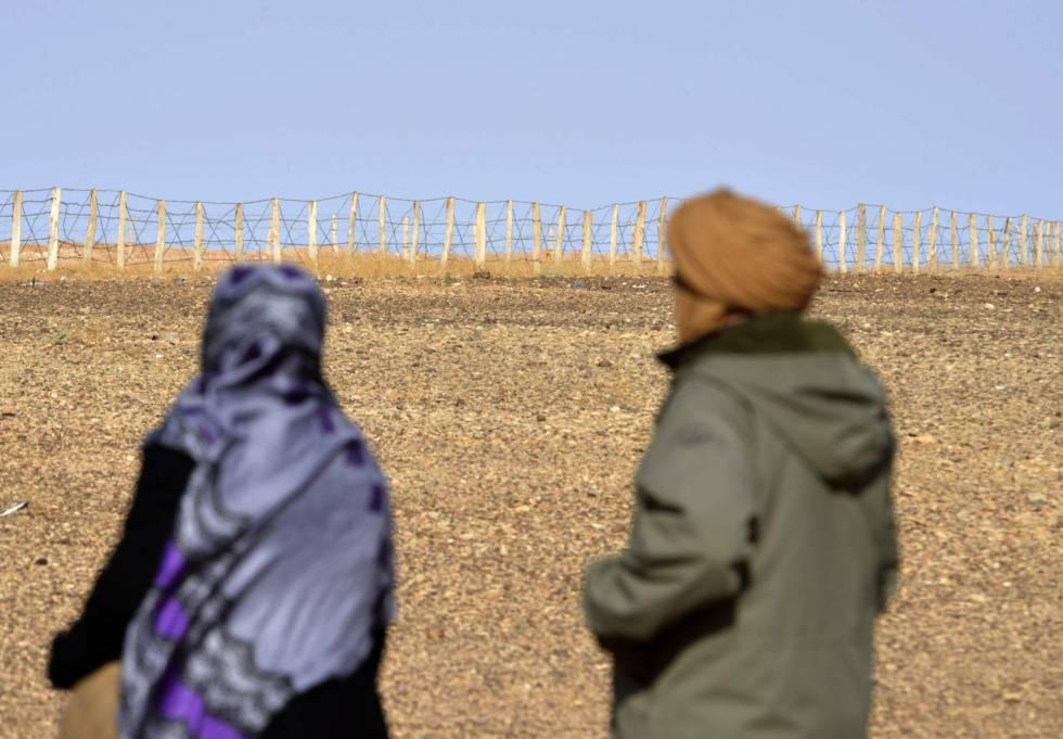 Duas pessoas contemplam a cerca que separa as zonas controladas pelo Marrocos e a Frente Polisário no Saara Ocidental.