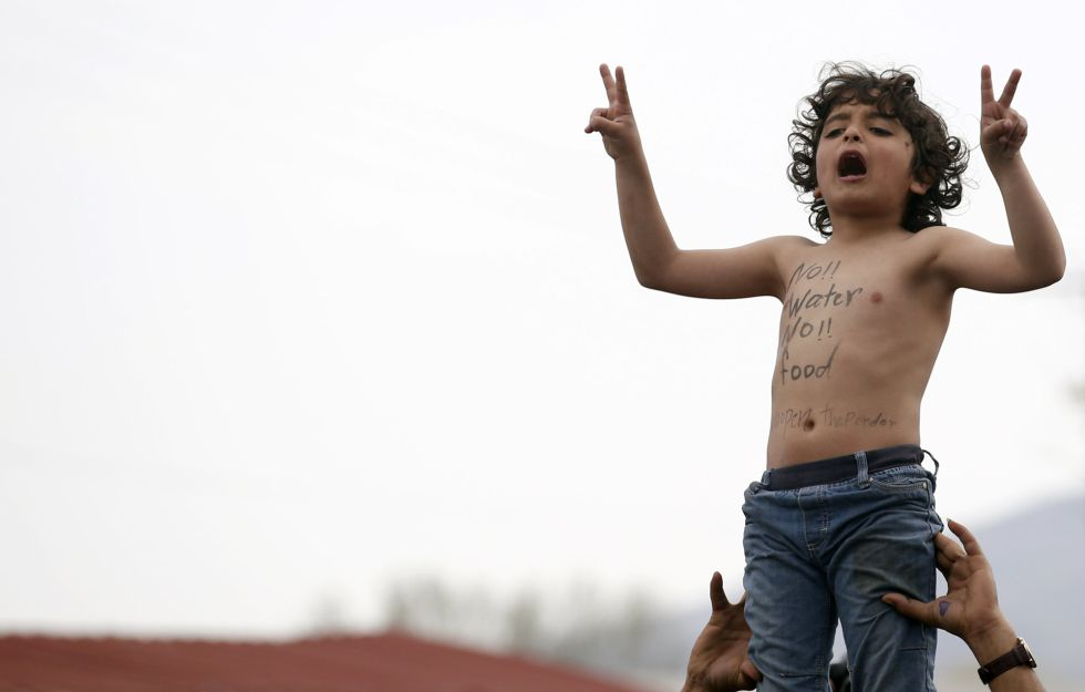"""Uma criança protesta na fronteira entre Grécia e Macedonia pela falta de água e alimentos. """"Nem água nem comida"""", diz o eslogan pintado no peito."""