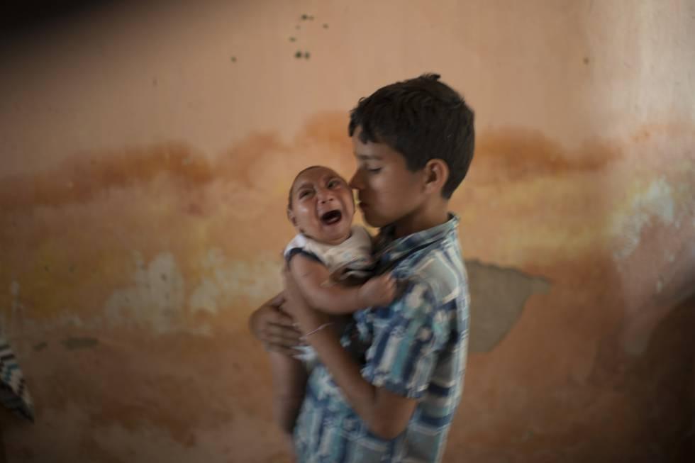 Elison, 10, segura o irmão José, 2 meses, que nasceu com microcefalia.