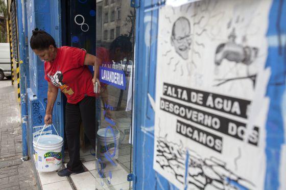 Funcionária de lavanderia busca água para ajudar a abastecer local.