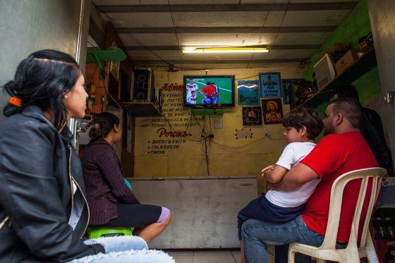 Um grupo de pessoas olha a final em uma favela de São Paulo.