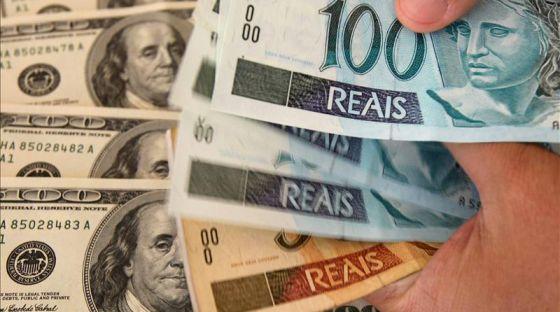 Notas de dólares norte-americanos e de reais brasileiros.