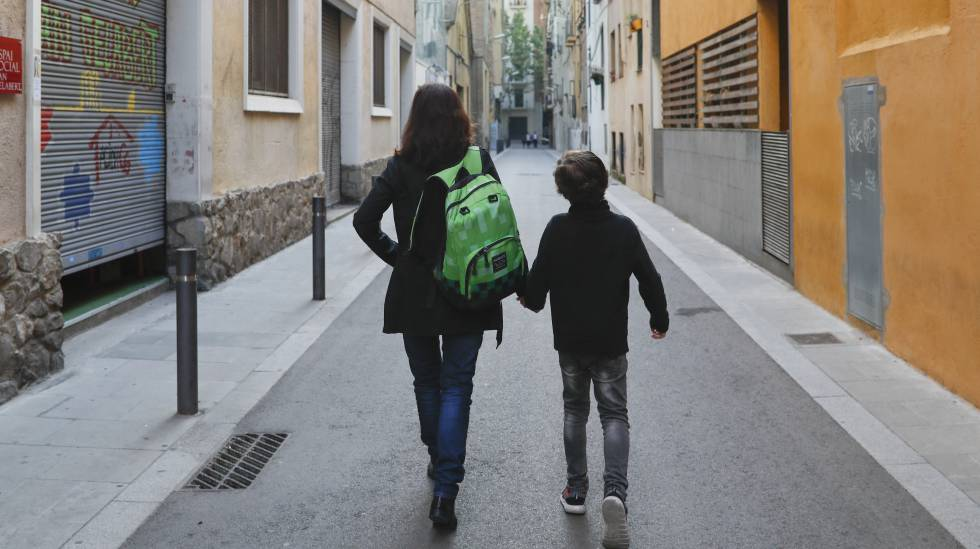 Uma mãe carrega a mochila de seu filho a caminho da escola