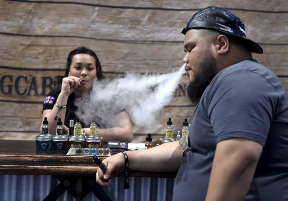 Duas pessoas fumam com cigarros eletrônicos em um encontro em Las Vegas.