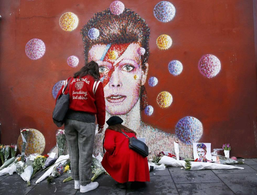 Mulheres deixam flores diante do mural de David Bowie em Brixton, no sul de Londres.