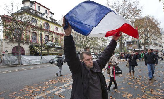 Um homem ergue a bandeira da França em frente ao Bataclan.