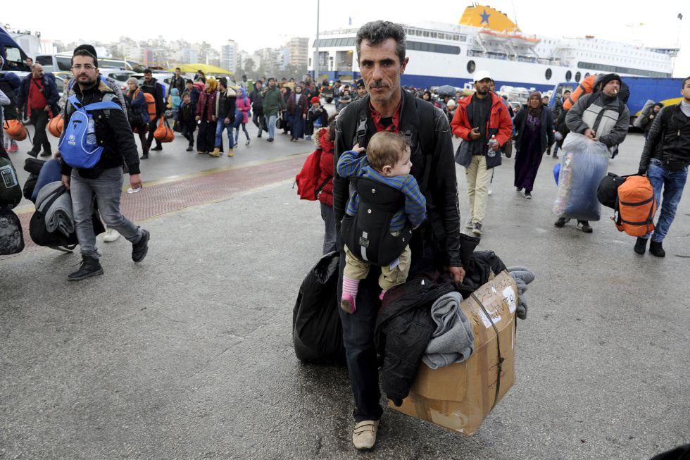 Um imigrante com um bebê chega na terça-feira a Atenas vindo das ilhas gregas.