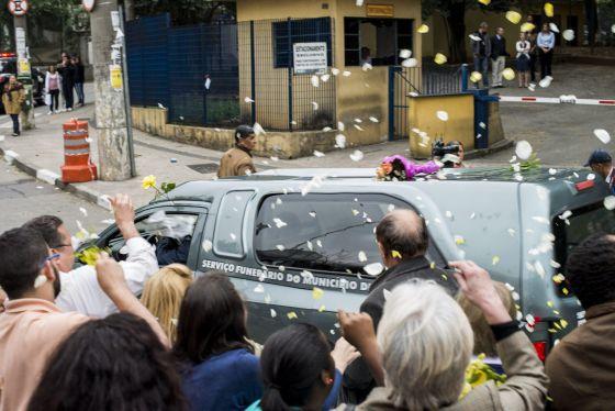Pessoas jogam pétalas sobre o carro com os restos mortais das vítimas.