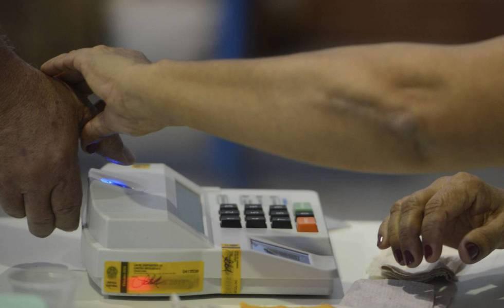 Mesária colhe digital de eleitor na eleição municipal de 2016 em Niterói.