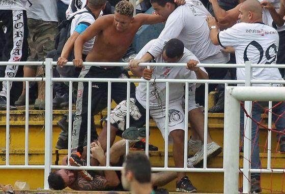 Torcedores em confronto na partida entre Vasco e Atlético Paranaense. AFP PHOTO/HEULER ANDREY