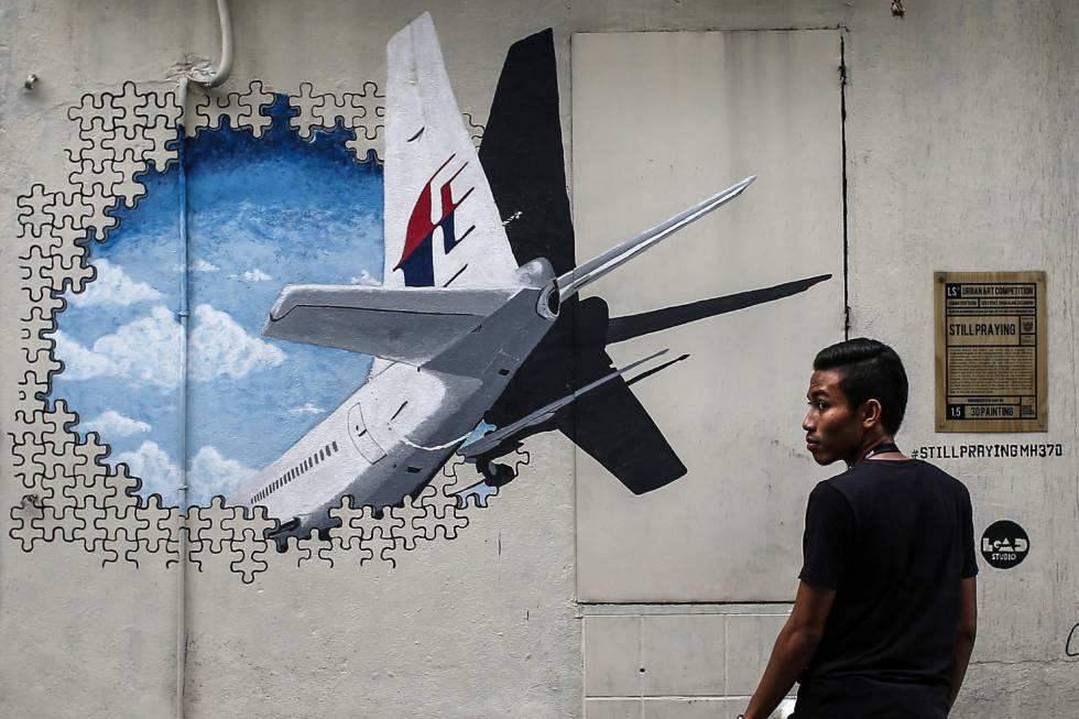 Um homem caminha ao lado de um mural em homenagem ao voo MH370 em Shah Alam, nos arredores de Kuala Lumpur (Malásia), em março de 2015.