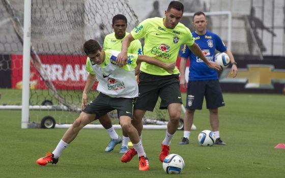 Oscar e Renato Augusto disputam a bola durante treino.