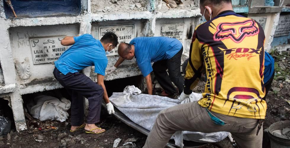 Funcionários do instituto médico legal enterram o corpo de uma vítima de assassinato extrajudicial não reclamado pela família.