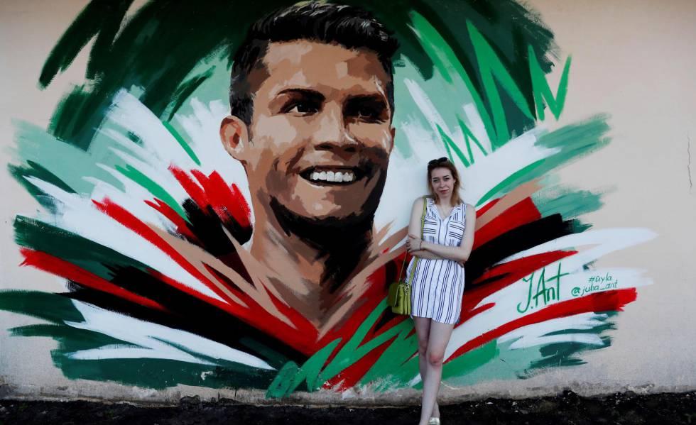 A artista Julia Antipova posa em frente ao mural que fez para Cristiano Ronaldo, em Saransk.