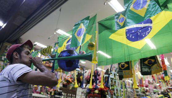 Um homem toca vuvuzela em frente a uma loja de São Paulo. O instrumento está proibido nos estádios.