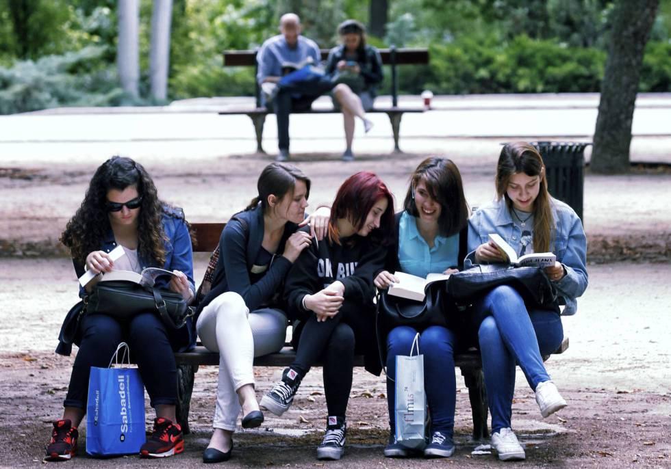 Grupo de jovens lê num banco na Feira do Livro de Madri.