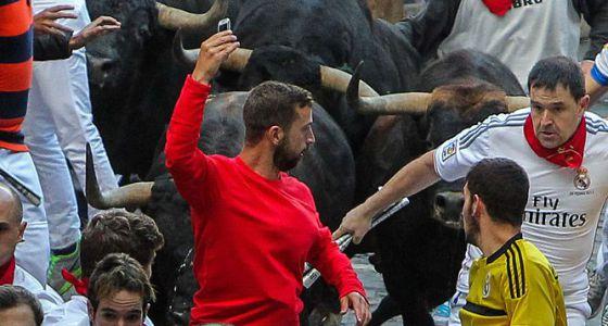 Corredor arrisca um 'selfie' diante de um touro em corrida de 2014.