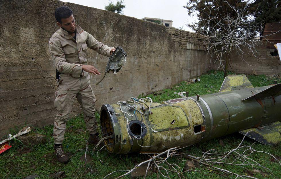 Um rebelde sírio inspeciona um foguete na terça-feira em uma área entre Daraa e Quneitra (Síria).