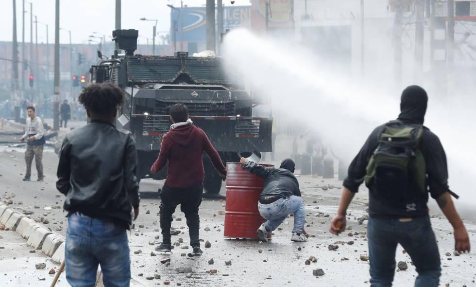 A polícia antidistúrbios em frente a um grupo de manifestantes nesta sexta-feira, em Bogotá.
