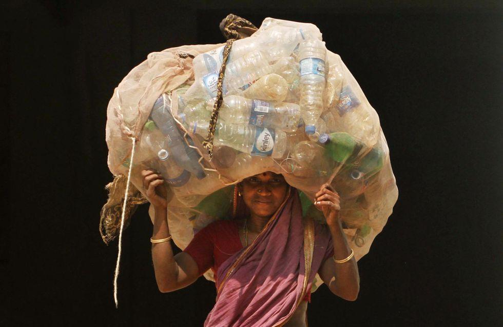 Mulher indiana carrega garaffas pet para vender em um centro de reciclagem, em Bhubaneswar.