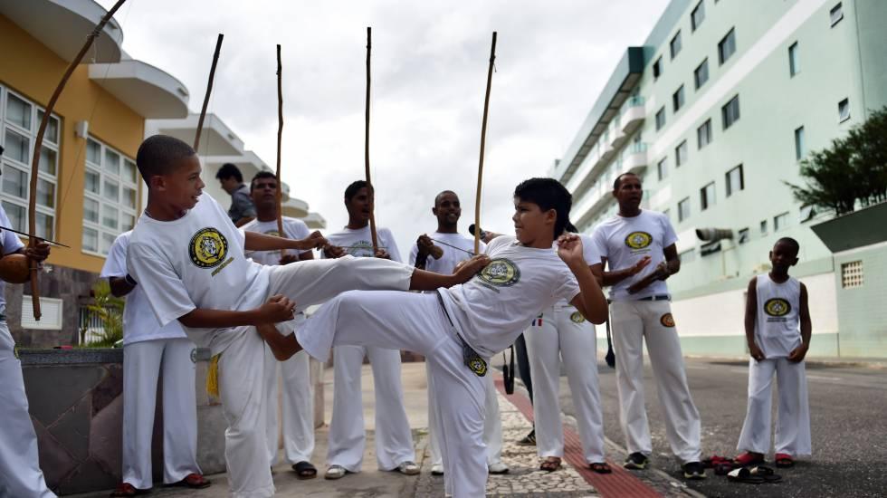 Crianças jogam capoeira