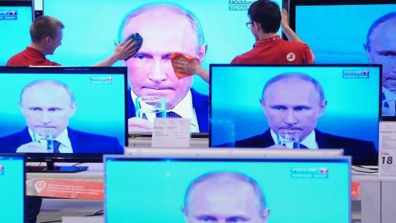 Funcionários de uma loja limpam uma tela de televisão durante pronunciamento do presidente Vladimir Putin, na quinta-feira, em Moscou.