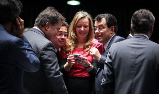 Senadores olham telefone celular no plenário.