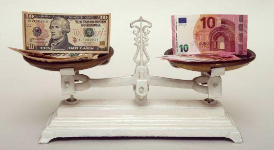 Notas de 10 dólares e 10 euros em uma balança.