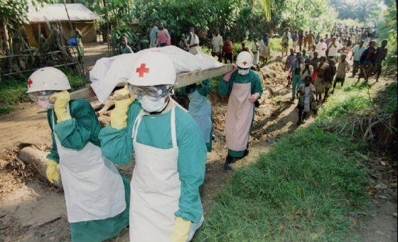 Membros da Cruz Vermelha transportam o cadáver de uma vítima de ebola, em 1995, perto de Kikwit, no Zaire.