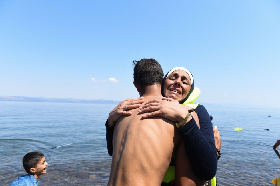 Abraço entre dois imigrantes após chegar à costa da ilha grega de Lesbos.