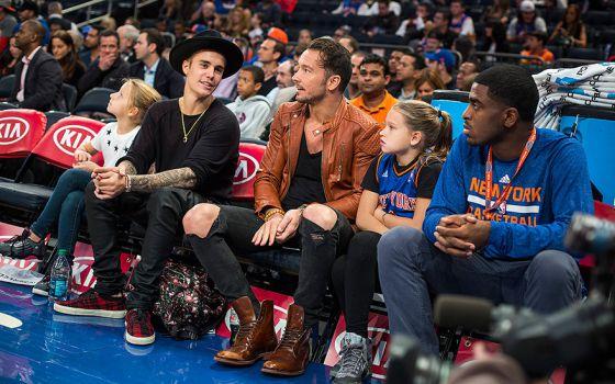 Carl Lentz, no centro, com suas filhas em uma partida dos Knicks. À sua direita, Justin Bieber.
