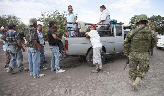 Membros do Exército mexicano inspecionam veículos na estrada que liga Apatzingán a Aguililla (Michoacán) dia 24 de janeiro.