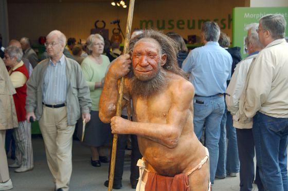 Estátua de um homem de neandertal na porta de um museu.