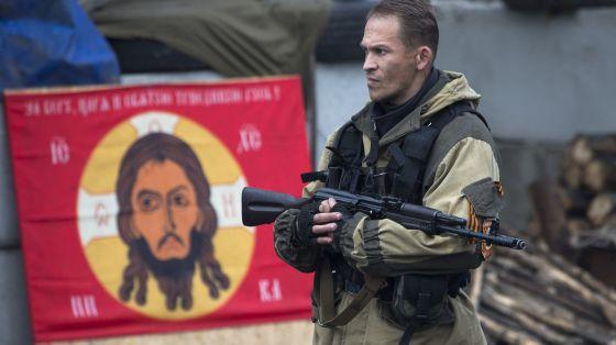 Um rebelde ucraniano diante de uma bandeira do Batalhão Ortodoxo Russo.