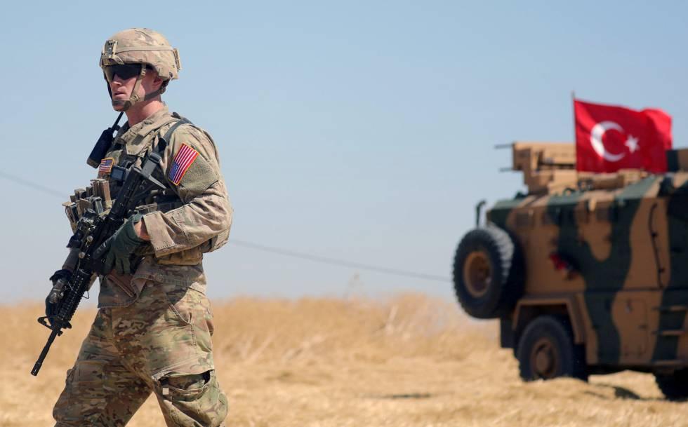 Soldado norte-americano caminha próximo de um veículo militar turco durante patrulha conjunta ao norte da região síria de Tel Abiad, em setembro