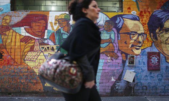 Mulher passa por grafite em Buenos Aires nesta sexta-feira.