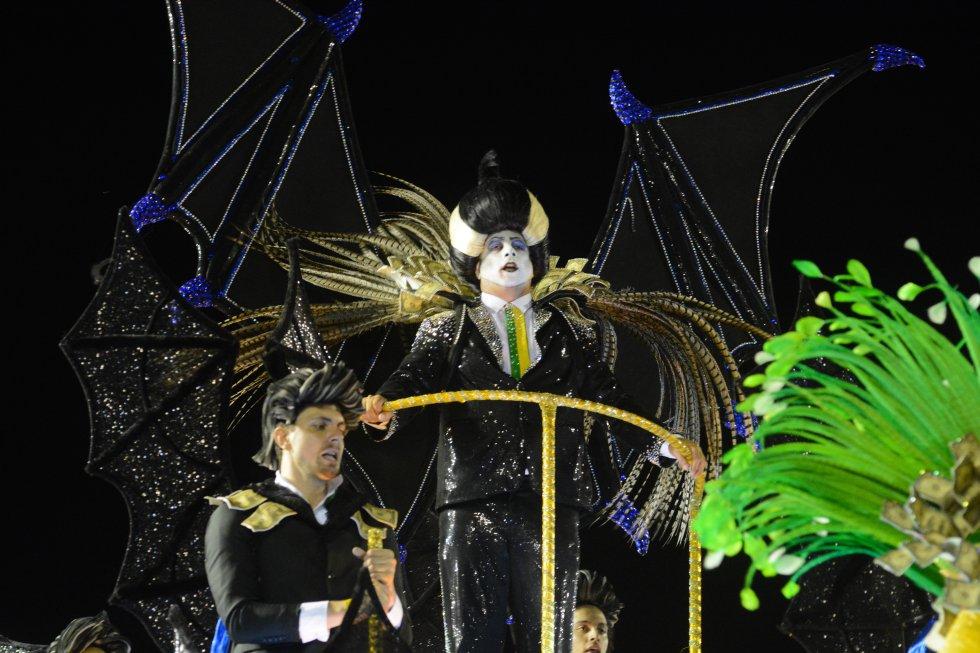 """A Paraíso do Tuiuti, escola vice-campeã e sensação do Carnaval do Rio, voltou à avenida neste sábado, mas com uma controvérsia. O destaque vestido de """"vampiro neoliberal"""", uma das fantasias mais comentadas do ano, desfilou sem a faixa presidencial da primeira aparição, que o transformou imediatamente em """"vampiro-presidente"""". As explicações da escola e do próprio folião foram contraditórias. O destaque Leo Morais primeiro disse ao G1 que esperava autorização para desfilar com a roupa completa, depois disse ter perdido a faixa. O jornal 'O Globo' citou fontes anônimas da escola para afirmar que a agremiação sofreu pressões da Presidência da República para censurar o adereço, porque o Planalto estaria incomodado com a representação do vampiro-presidente. O assunto virou um dos temas mais comentados das redes sociais."""