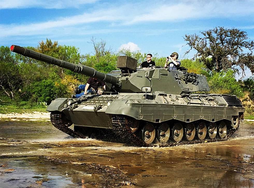 Visitantes do parque Drive Tank conduzem um tanque de guerra.