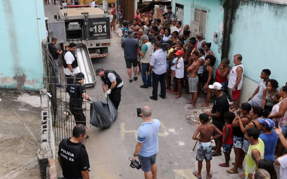 Moradores de Vitória observam a Polícia Civil retirar um corpo em uma rua no Espírito Santo, nesta sexta-feira.