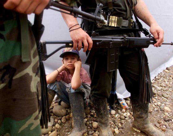 Um menino e os guerrilheiros das FARC em San Vicente de Calguán, no ano 2000.