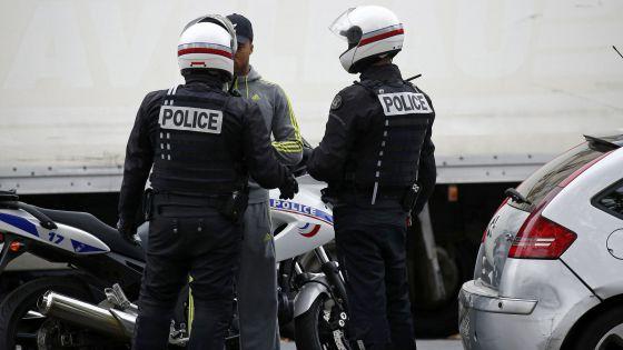 Policial francesa revista um homem no centro de Paris.