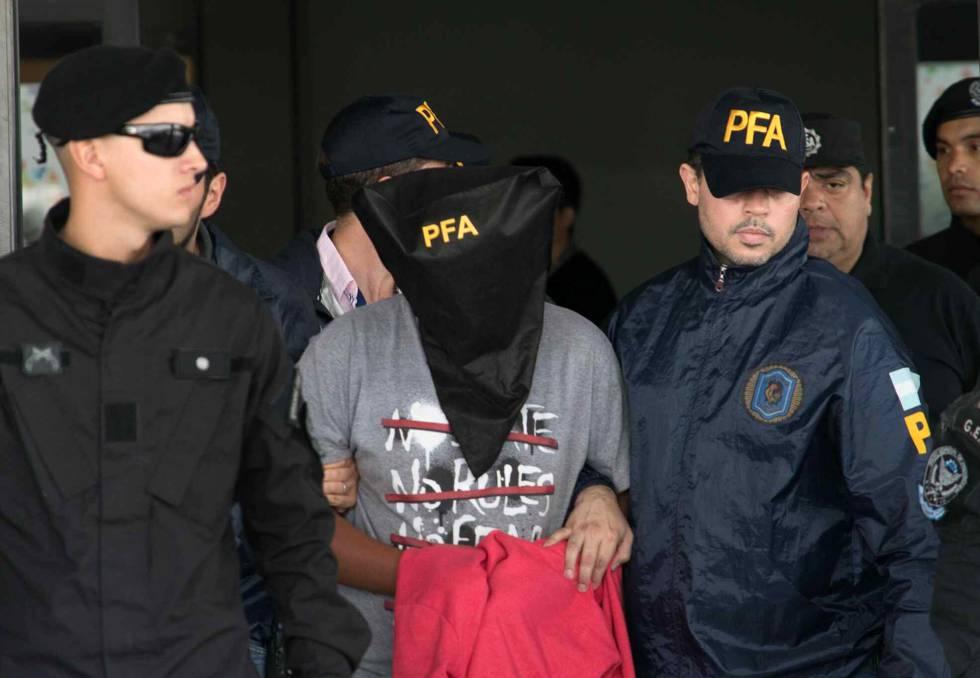 Adolescente de 15 anos é conduzido por policiais no aeroporto de Ezeiza, em Buenos Aires, sob a acusação de matar outro menor no bairro de Flores.