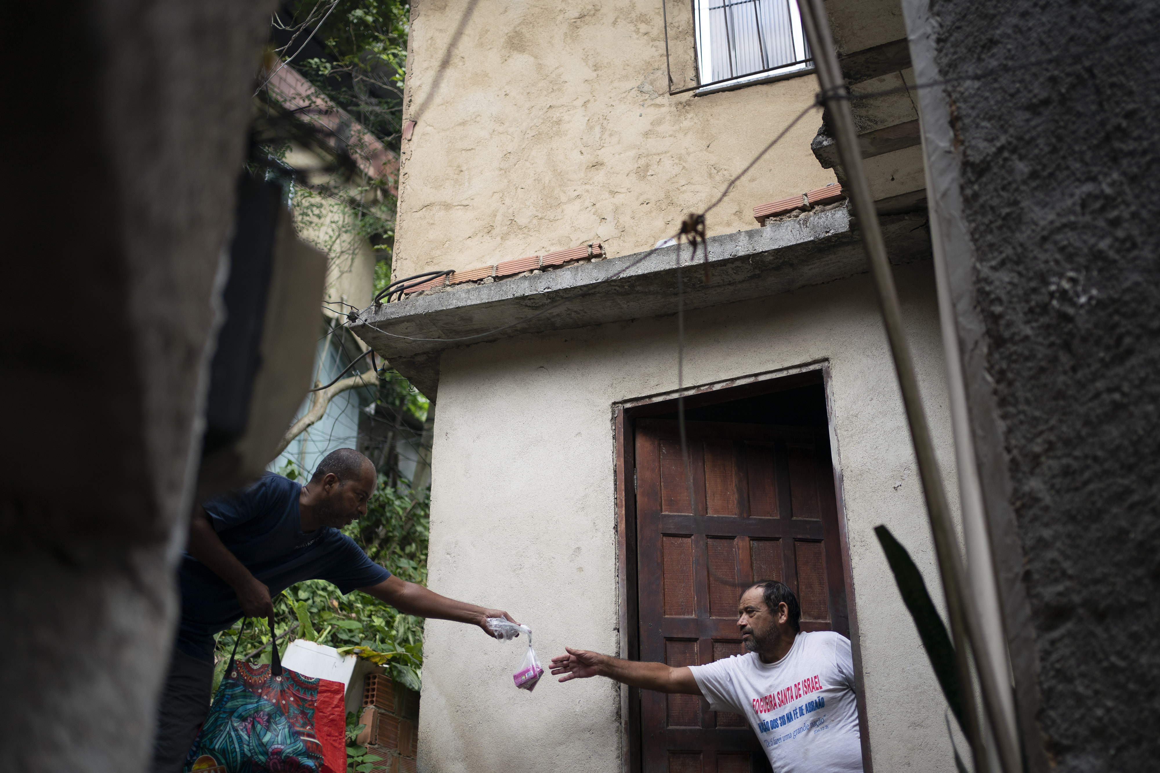A local volunteer hands soap to a resident in an effort to avoid the spread of the new coronavirus in the Rocinha slum of Rio de Janeiro, Brazil, Tuesday, March 24, 2020. (AP Photo/Leo Correa)