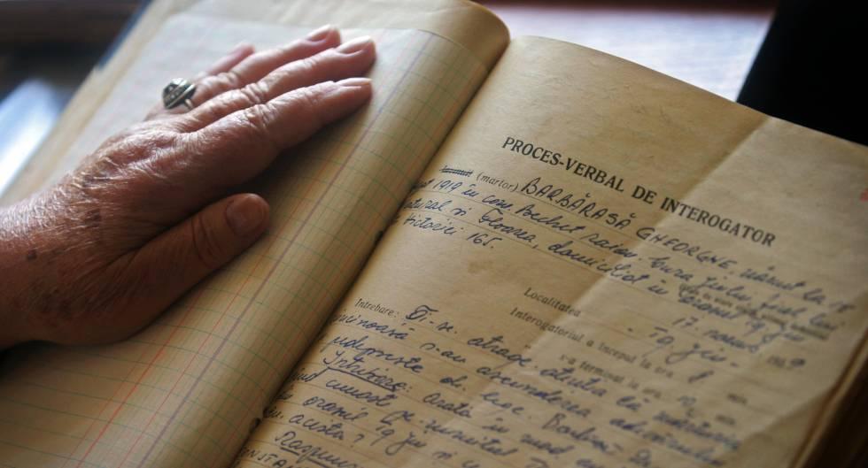 Uma mulher consulta um relatório da Securitate romena.