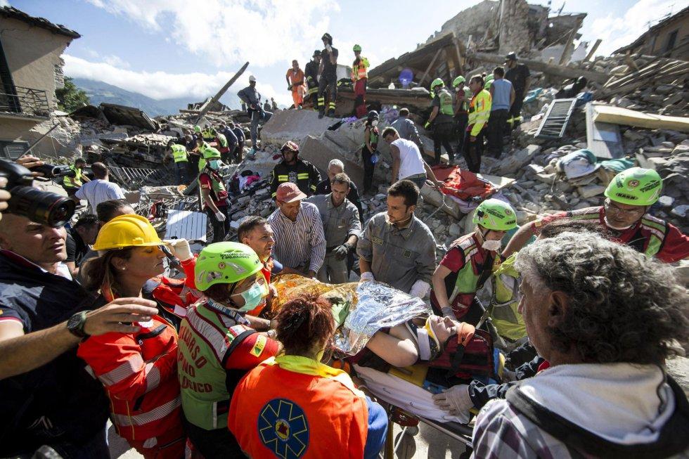 Mulher é transportada em uma maca pelas equipes de resgate, em Amatrice (Itália).