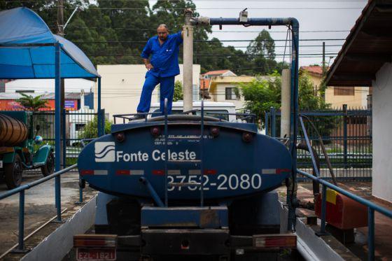 Motorista carrega tanque de um caminhão-pipa em São Paulo.