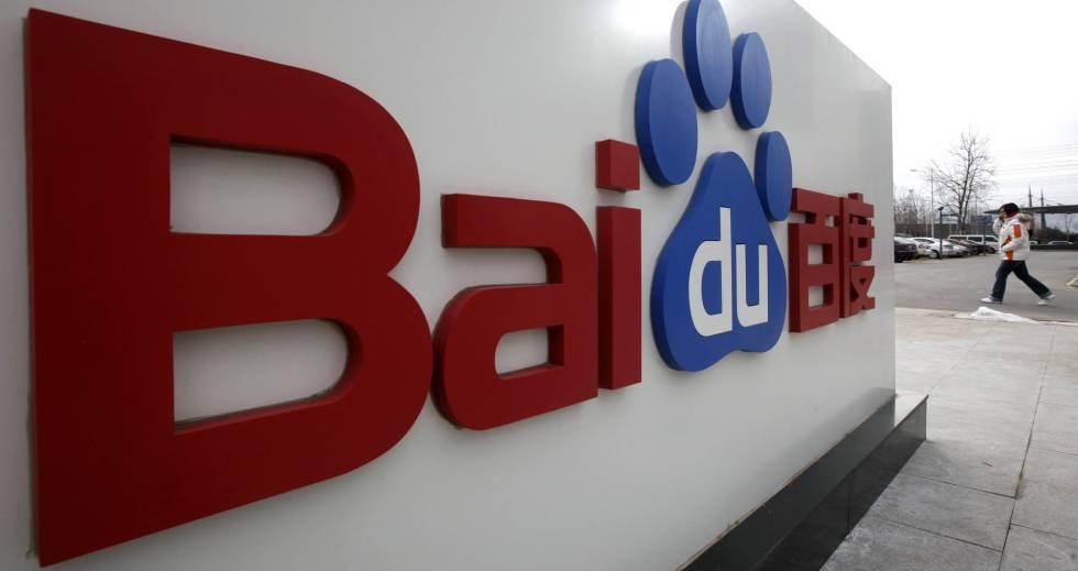 Uma mulher caminha junto ao logótipo de Baidu em sua sede de Beijing.