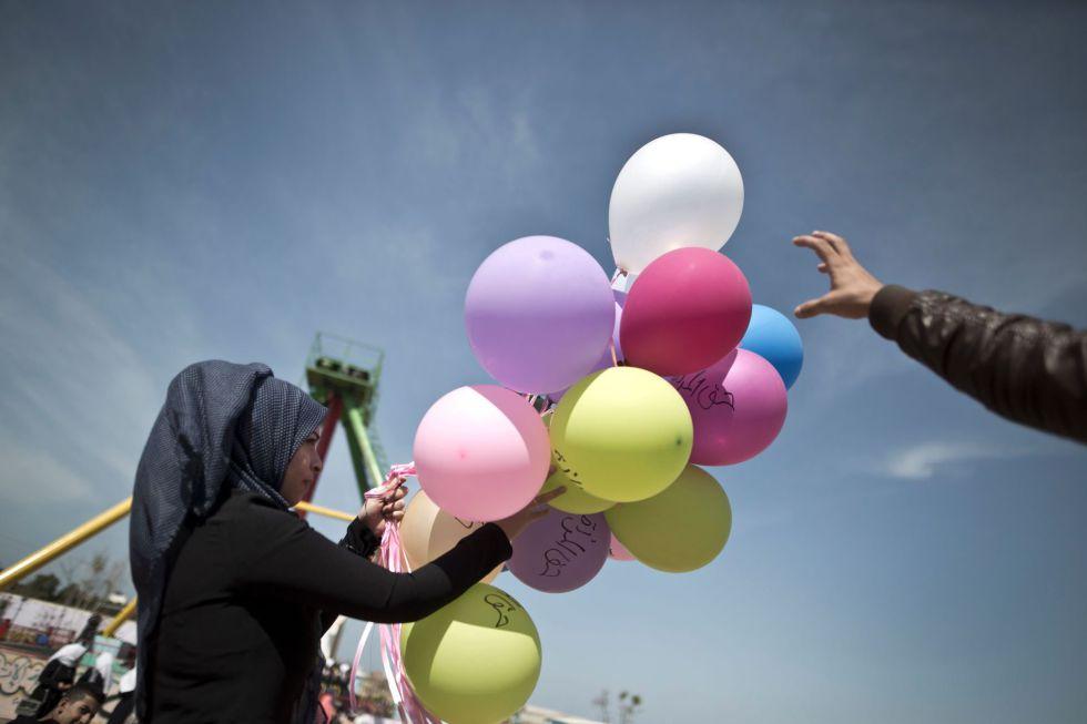 Jovem palestina carrega balões com frases que lembram o Dia Internacional da Mulher, nesta terça-feira, em Gaza.