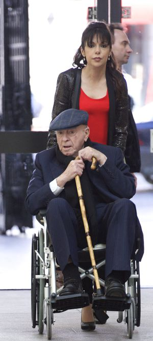 Alfredo di Stéfano in a wheelchair being pushed by his girlfriend.